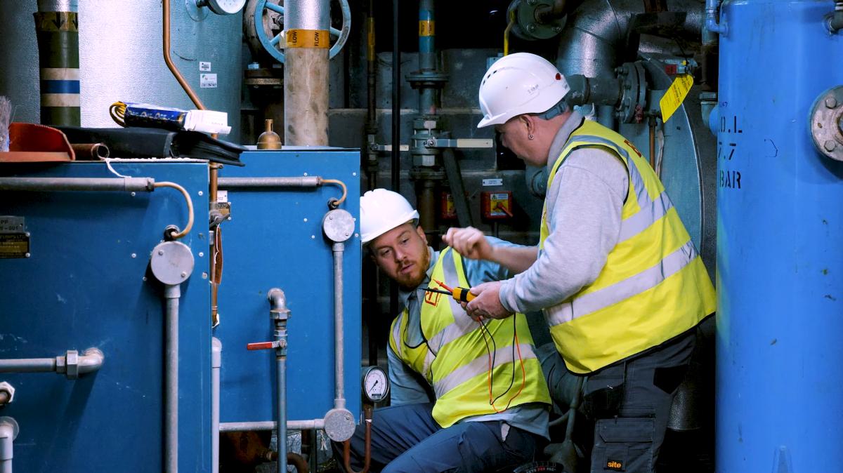 Two men repairing a boiler