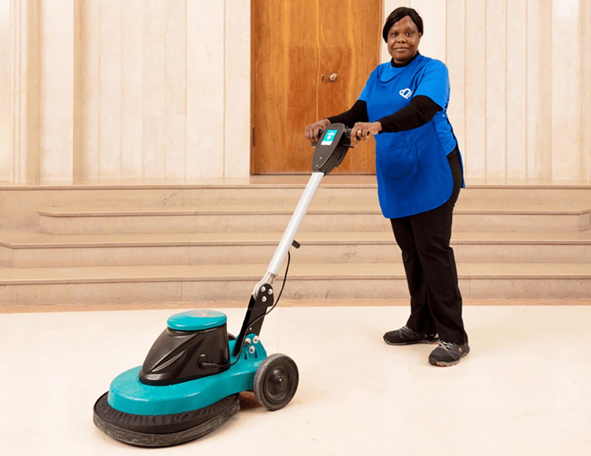 Woman holding a floor polishing machine